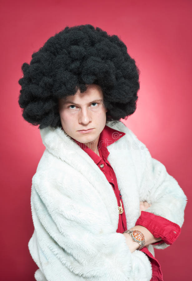 Pimp. Arrogantly looking man, wearing a wig and a fur coat royalty free stock images