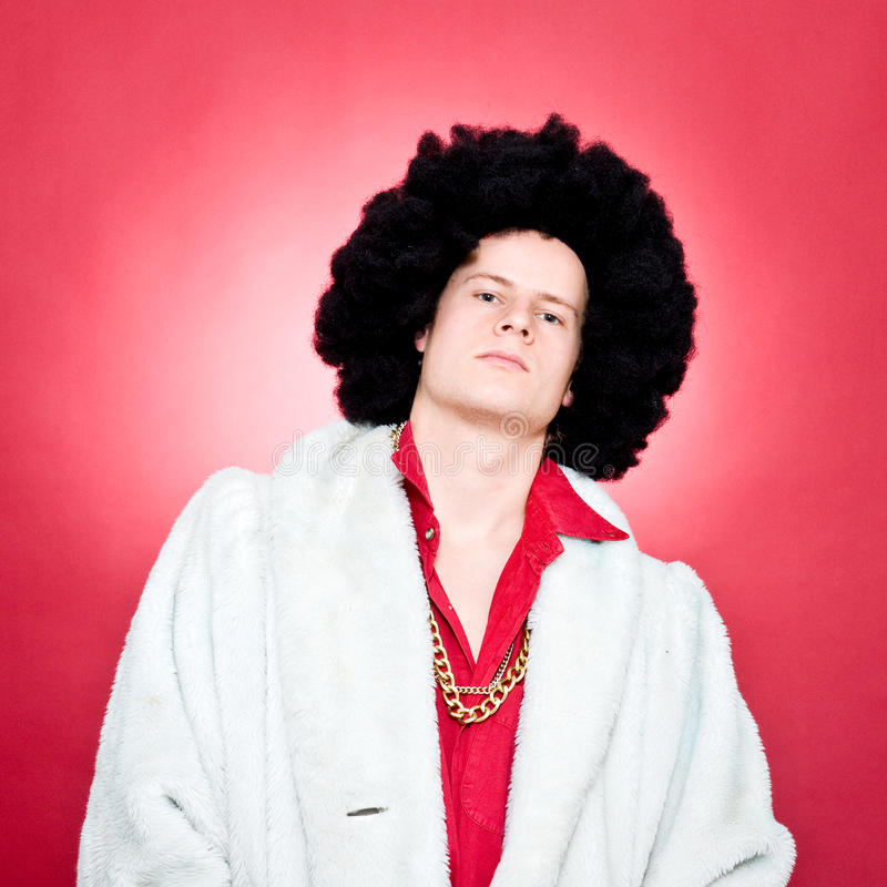 Pimp. Arrogantly looking man, wearing a wig and a golden chain stock photos