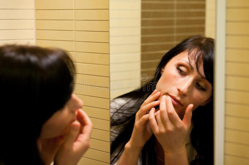 Pimple woman. Woman squeezing a pimple looking in mirror royalty free stock photos