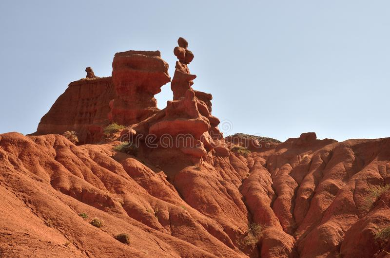 Pináculos rojos de las rocas de la piedra arenisca de la garganta de Konorchek, Kyrgyzian Grand Canyon, señal natural famosa y lu fotografía de archivo