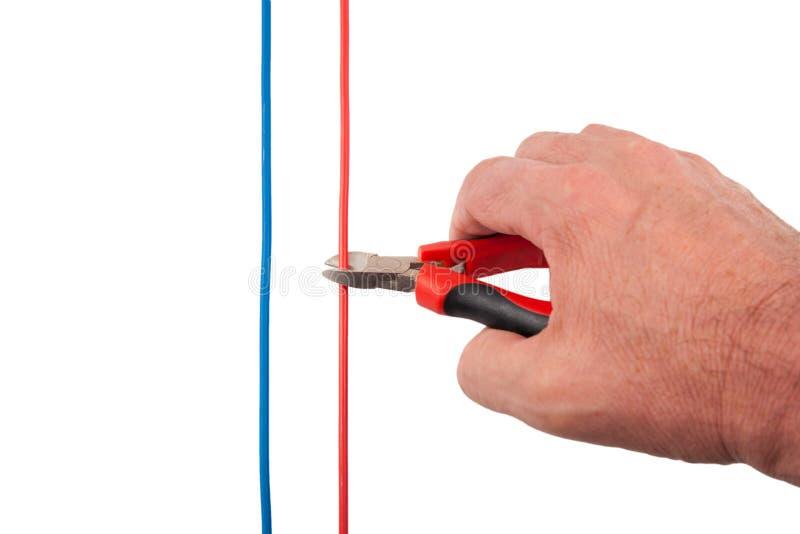 Pinças que cortam o fio vermelho fotografia de stock