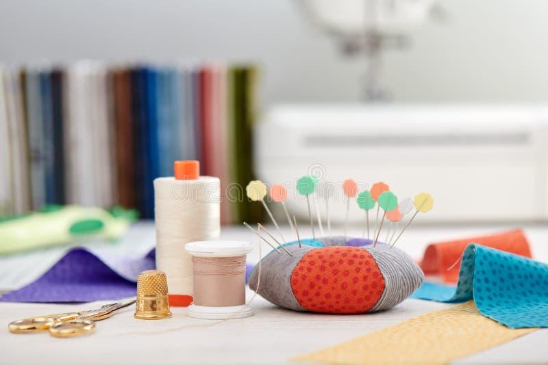 Pin坐垫、织品明亮地彩带,在堆背景的缝合的辅助部件织品和缝纫机 库存图片