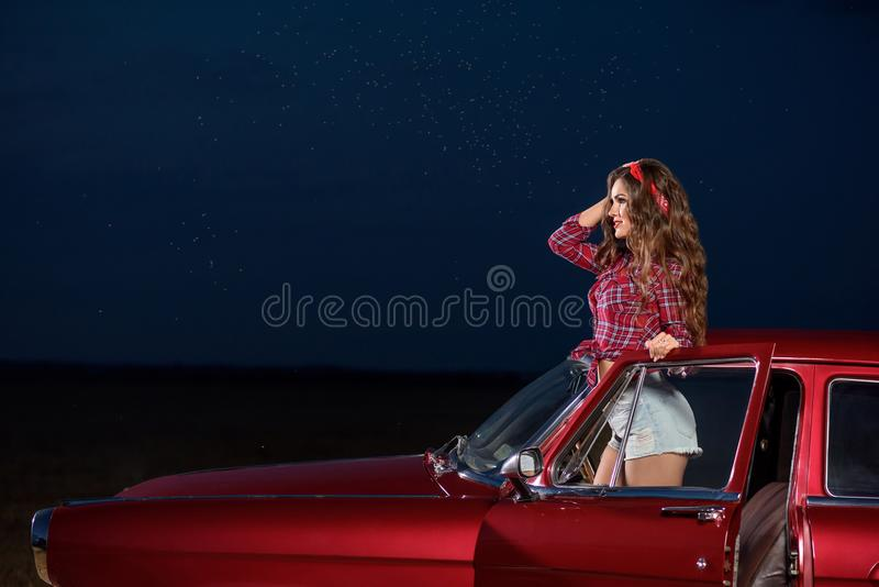 Pin acima da menina que levanta com antiquado, carro retro e céu do ` s da noite com estrelas foto de stock