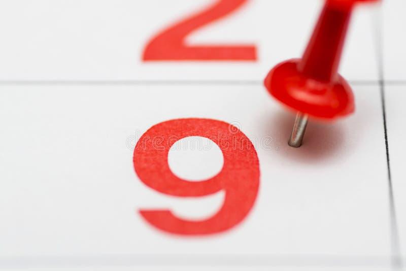Pin auf dem Datum Nr. 9 Der 9. Tag des Monats wird mit roten Reißzwecken markiert Pin auf Kalender stockfoto