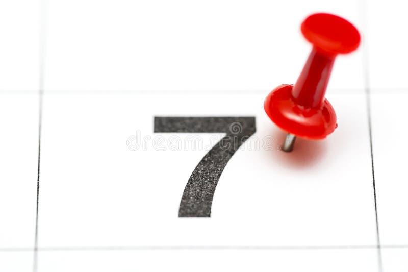 Pin auf dem Datum Nr. 7 Der 7. Tag des Monats wird mit roten Reißzwecken markiert Pin auf Kalender stockfotografie