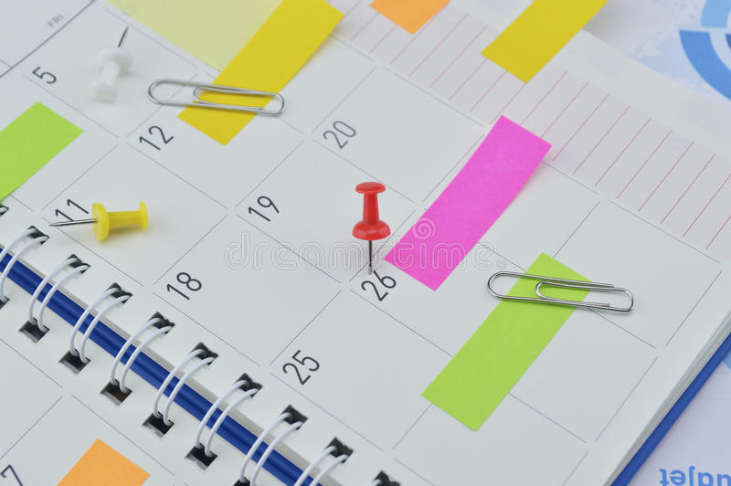 Pin with colorful sticky notes and pin on business diary page royalty free stock photo