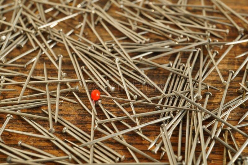 Pin con un agrostide bianco sulla cima del mucchio di molti perni d'argento utilizzati nell'industria di indumento dell'abbigliam immagine stock