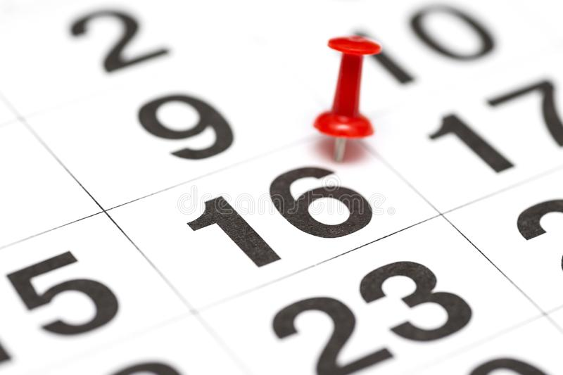 Pin on the date number 16. The sixteenth day of the month is marked with a red thumbtack. Pin on calendar.  stock photos