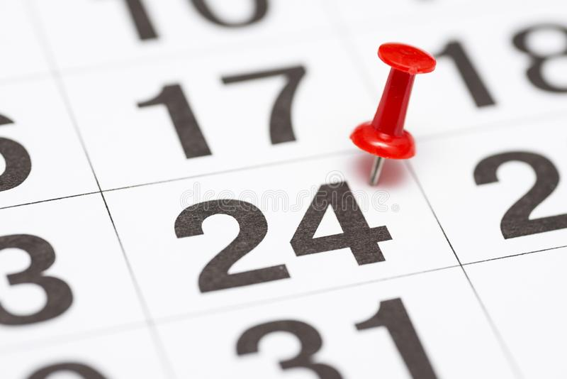 Pin on the date number 24. The twenty fourth day of the month is marked with a red thumbtack. Pin on calendar.  stock images