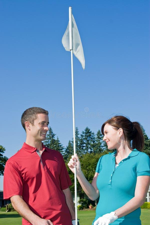 Pin do golfe da terra arrendada do homem e da mulher - vertical fotos de stock royalty free