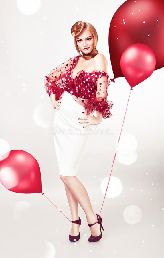 Pin encima de la mujer rubia atractiva en blusa roja fotografía de archivo