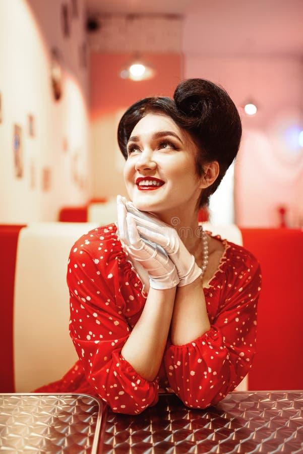 Pin herauf Mädchen mit den roten Lippen, die im Retro- Café sitzen stockbilder