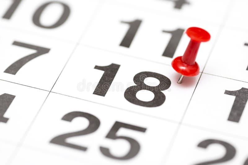 Pin la date numéro 18 Le dix-huitième jour du mois est identifié par une punaise rouge Pin sur le calendrier Concept de calendrie photographie stock libre de droits