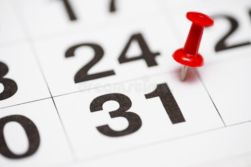 Pin la date numéro 31 Le premier jour trente du mois est identifié par une punaise rouge Pin sur le calendrier photographie stock libre de droits