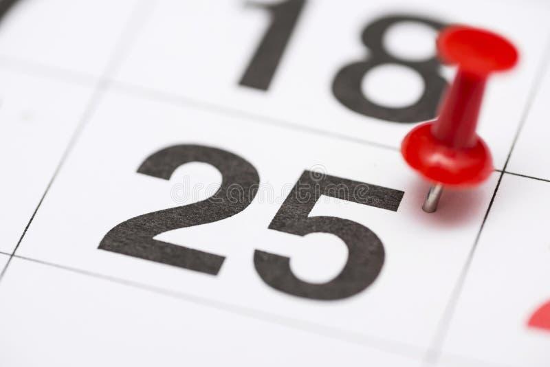 Pin la date numéro 25 Le vingt-cinquième jour du mois est identifié par une punaise rouge Pin sur le calendrier images stock