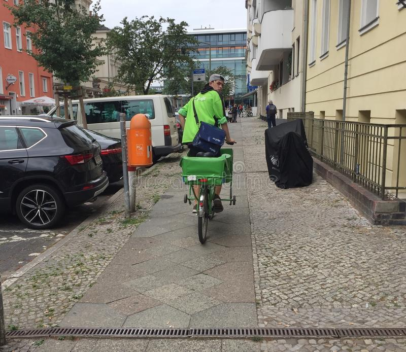 Pin Mail delivery man on green bike. Berlin, Germany - June 20, 2018: Pin Mail delivery man on a green bicycle. Pin Mail AG is a German private postal service royalty free stock photos