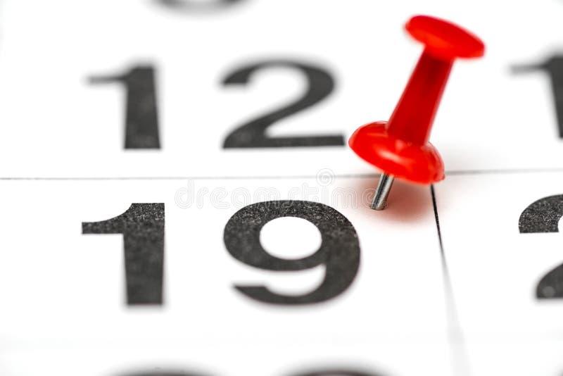 Pin na data número 19 O décimo nono dia do mês é identificado por meio de um percevejo vermelho Pin no calendário imagens de stock
