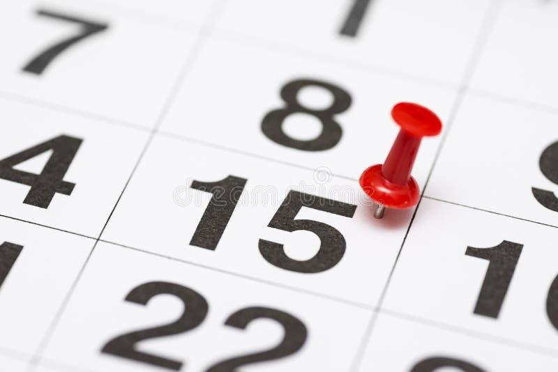 Pin na data número 15 O décimo quinto dia do mês é identificado por meio de um percevejo vermelho Pin no calendário fotos de stock
