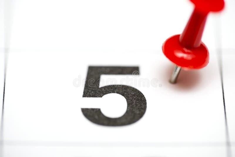 Pin na data número 5 O quinto dia do mês é identificado por meio de um percevejo vermelho Pin no calendário imagem de stock