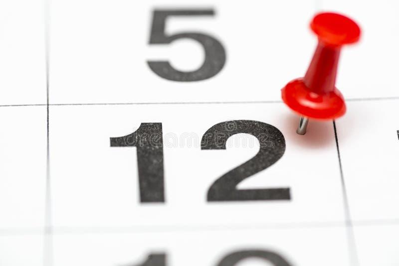 Pin na data número 12 O segundo dia vinte do mês é identificado por meio de um percevejo vermelho Pin no calendário imagem de stock