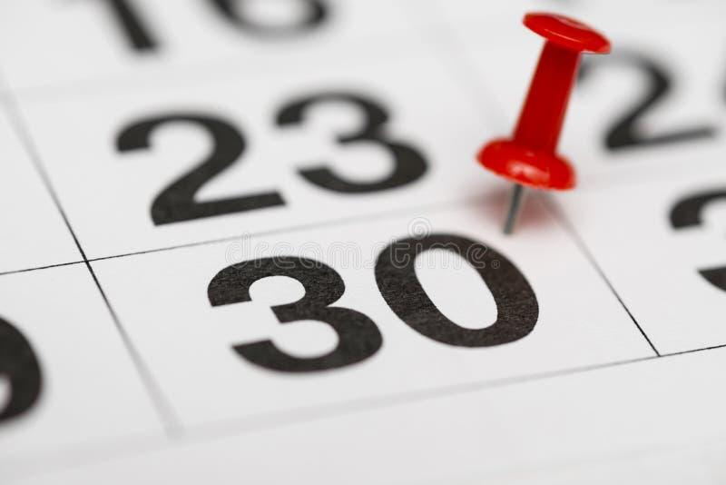Pin na data número 30 O trigésimo dia do mês é identificado por meio de um percevejo vermelho Pin no calendário imagem de stock
