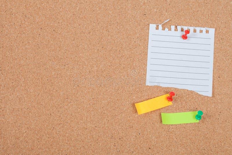 Pin no papel do memorando na placa da cortiça foto de stock