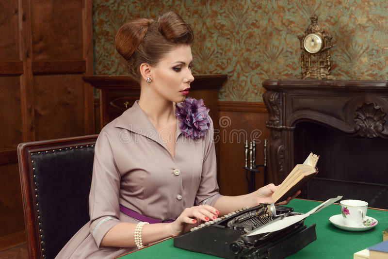 Pin Up beautiful young woman reading a book and prints on an old typewriter in vintage interior. Pin-up beautiful young woman 50s American style in vintage stock photos