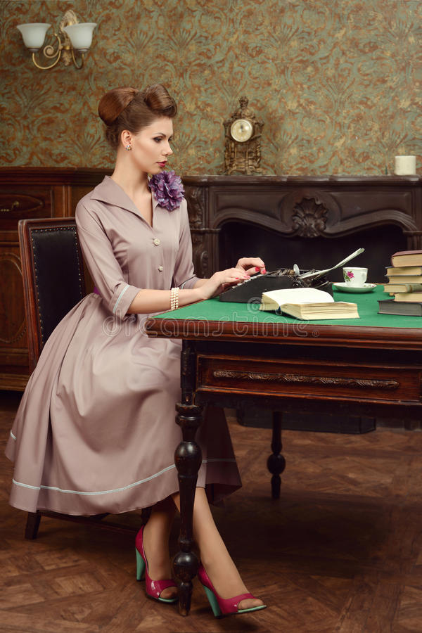 Pin Up beautiful young woman reading a book and prints on an old typewriter in vintage interior. Pin-up beautiful young woman 50s American style in vintage royalty free stock photo
