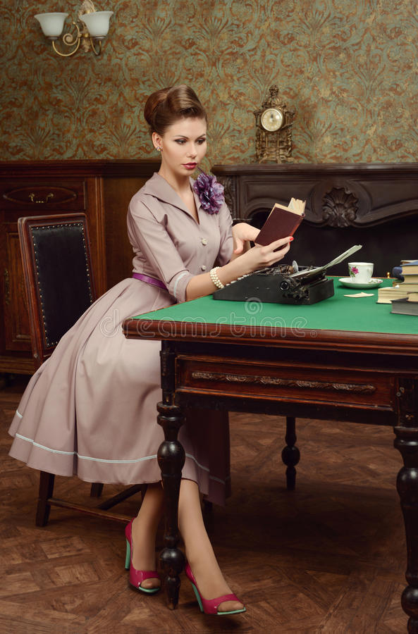 Pin Up beautiful young woman in vintage interior reading a book and prints on an old typewriter. Pin-up beautiful young woman 50s American style in vintage royalty free stock image