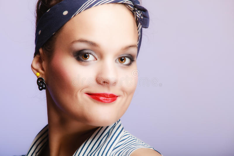 Pin-up del ritratto con il panino e fermaglio per capelli sulla viola Modo fotografie stock libere da diritti