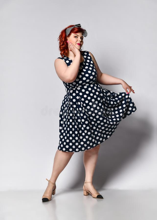 Pin up a female portrait. Beautiful retro fat woman in polka dot dress with red lips and manicure nails and old-style haircut.  stock images