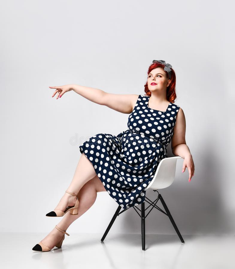 Pin up a female portrait. Beautiful retro fat woman in polka dot dress with red lips and old-style haircut. Cute young plus-sized girl wearing a polka-dot dress royalty free stock image