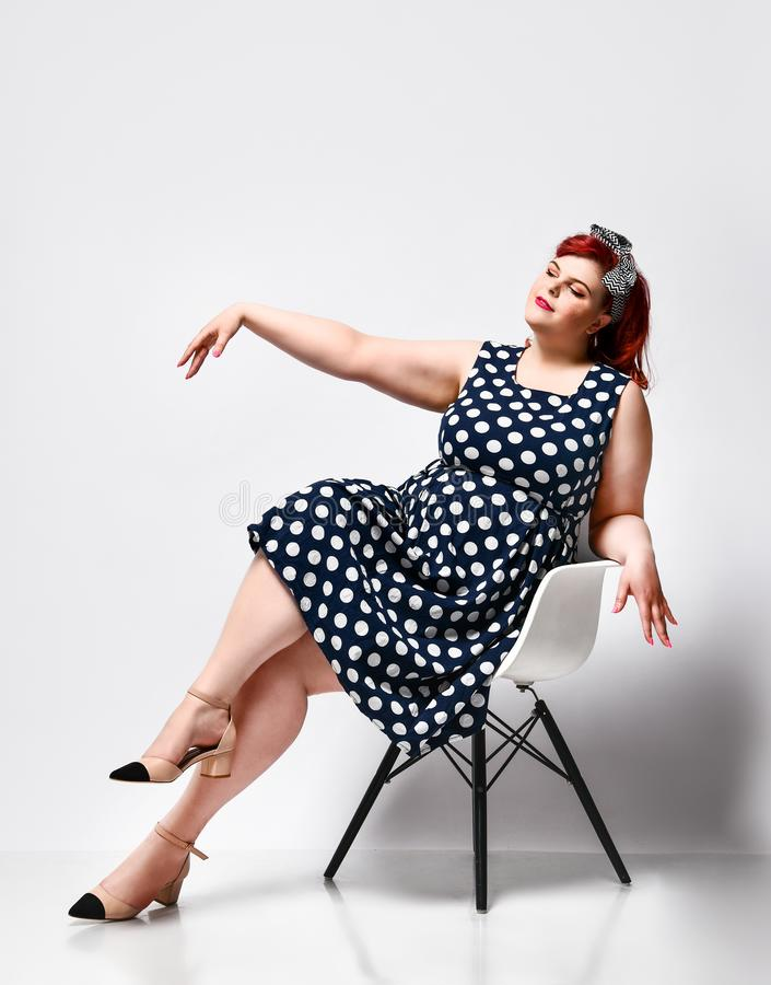 Pin up a female portrait. Beautiful retro fat woman in polka dot dress with red lips and old-style haircut stock photo