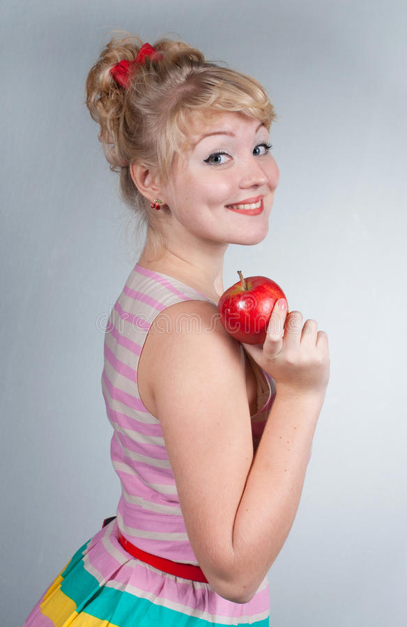 Pin-up girl with apple. Portrait of a beautiful blond pin-up girl with apple stock photo