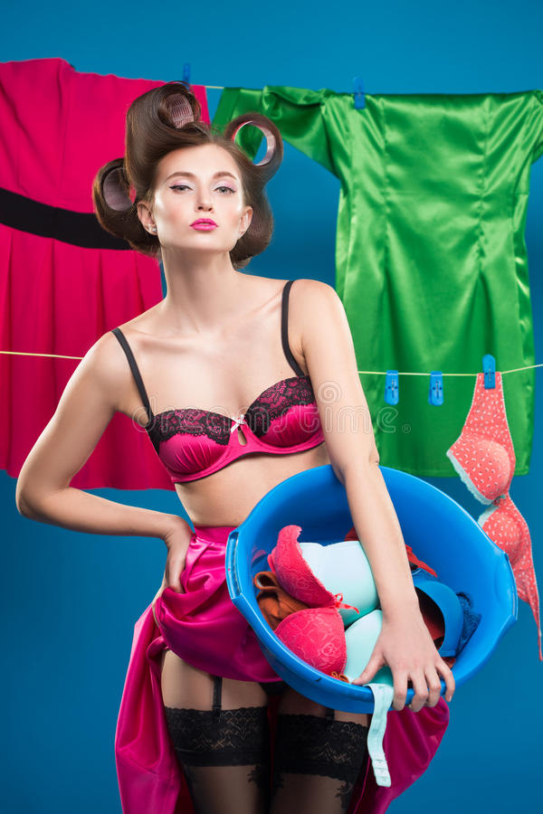 Pin-up girl with a basket with the laundry. Pin-up girl on the background of the ropes with the laundry royalty free stock image