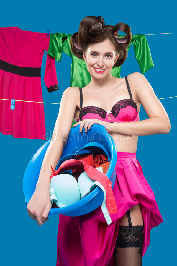 Pin-up girl with a basket with the laundry. Pin-up girl on the background of the ropes with the laundry royalty free stock photos
