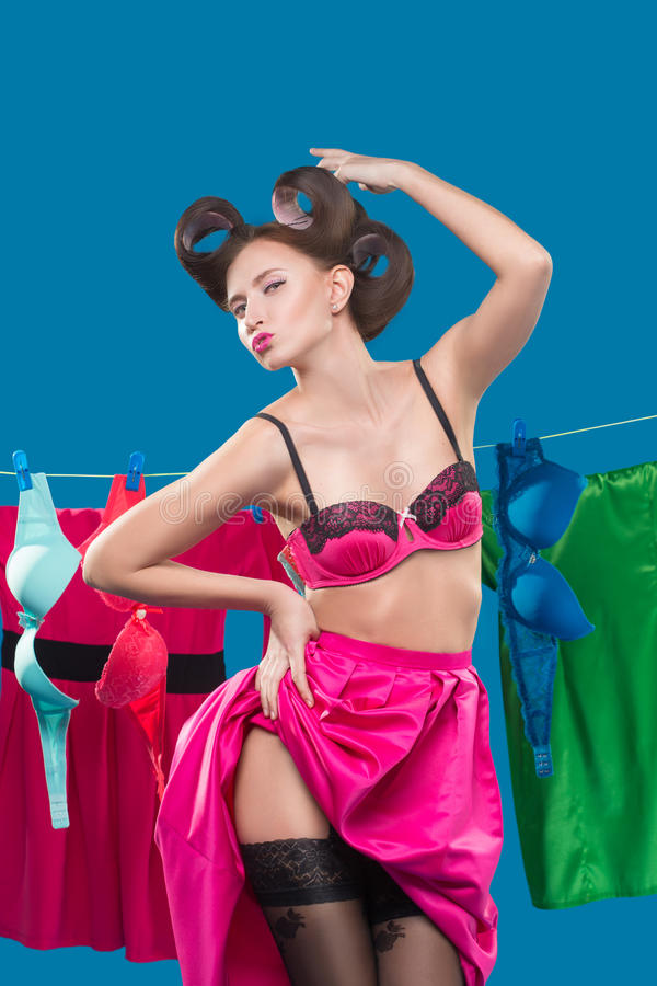 Pin-up girl with a basket with the laundry. Pin-up girl on the background of the ropes with the laundry stock photography