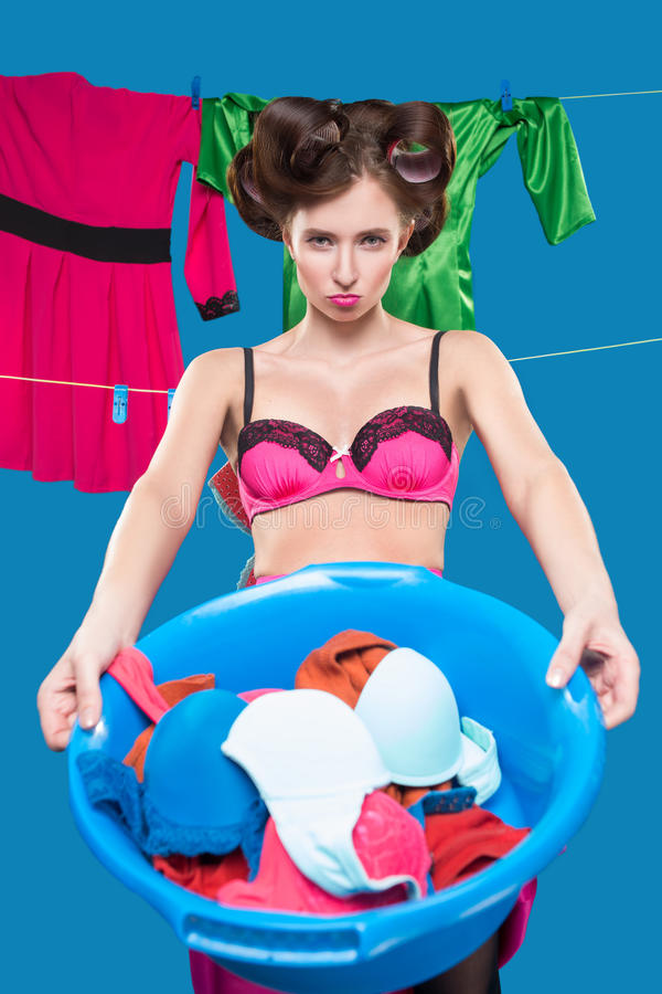 Pin-up girl with a basket with the laundry. Pin-up girl on the background of the ropes with the laundry royalty free stock images