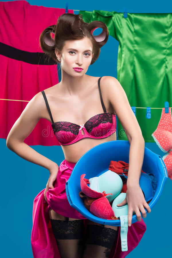 Pin-up girl with a basket with the laundry. Pin-up girl on the background of the ropes with the laundry stock photos