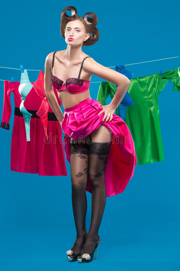 Pin-up girl with a basket with the laundry. Pin-up girl on the background of the ropes with the laundry stock images
