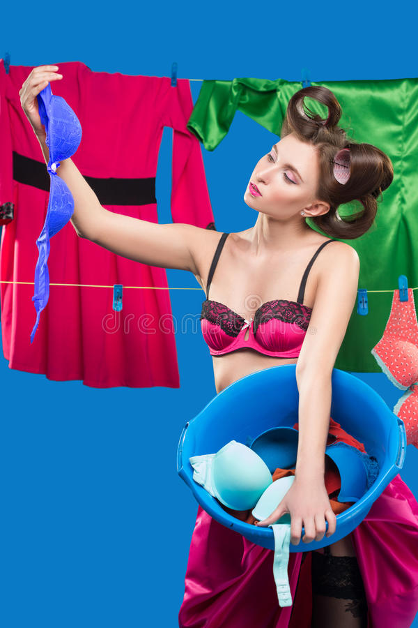 Pin-up girl with a basket with the laundry. Pin-up girl on the background of the ropes with the laundry stock image