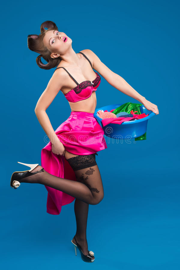 Pin-up girl with a basket with the laundry. Pin-up girl on the background of the ropes with the laundry royalty free stock photo