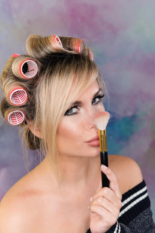 Pin up girl in curlers. Portrait of seductive sexy pin-up girl in curlers with full lips. Young attractive woman posing, fooling around and holding the hands of royalty free stock images