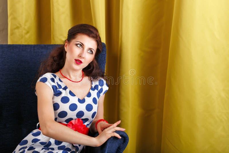 Pin-up-Girl, das in einem Stuhl sitzt lizenzfreies stockfoto