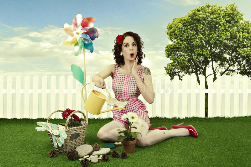 Pin up girl gardening. Pin up girl watering flower in a garden stock photos