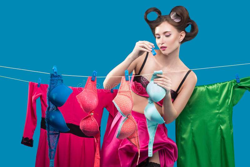 Pin-up girl hangs bras. Pin-up girl on the background of the ropes with the laundry royalty free stock photography