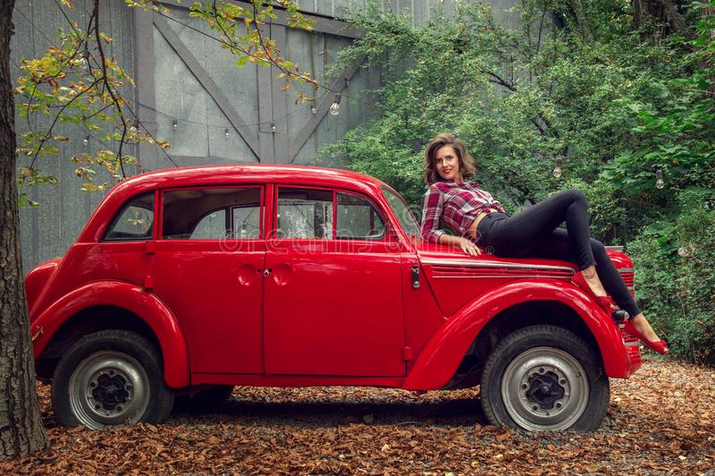 Pin-up girl in jeans and a plaid shirt is posing on a russian red retro car. She is looking at the camera and smiling happily royalty free stock images