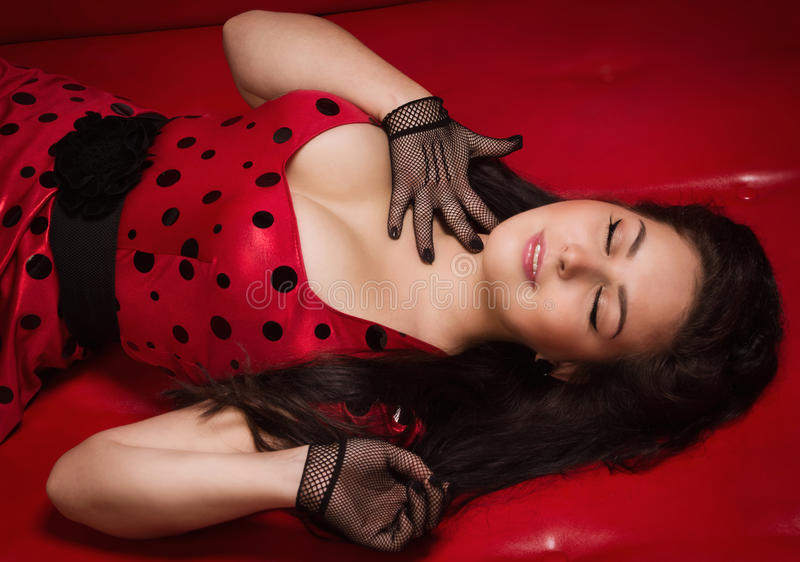 Pin-up girl lying on a red leather couch royalty free stock photography