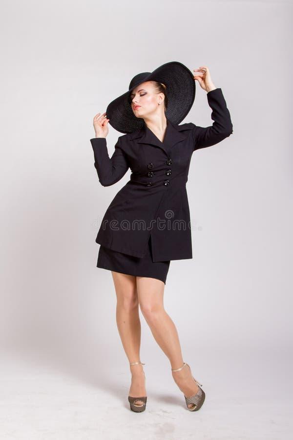 Pin-up-Girl mit einem großen schwarzen Hut stockbild