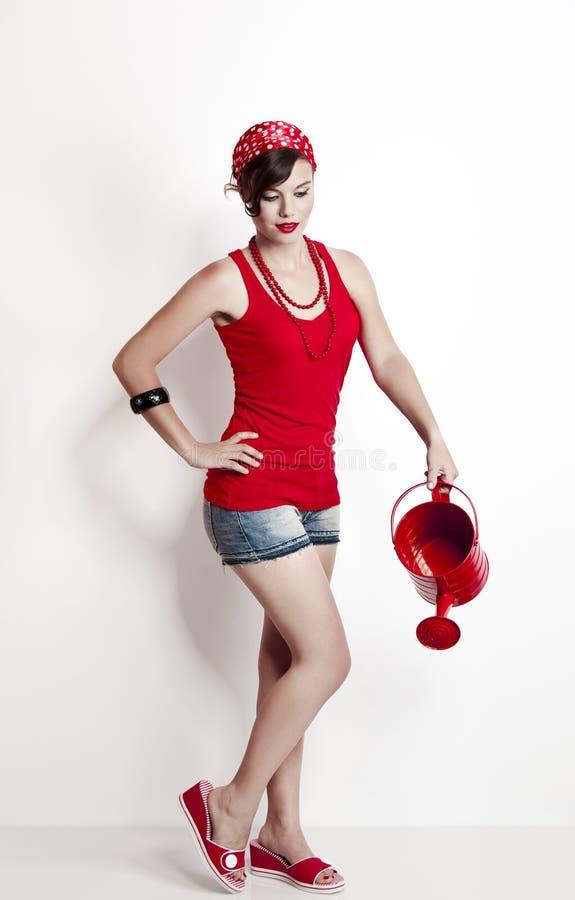 Pin-up-Girl mit einer Bewässerungsdose stockfotos